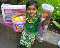 Make-A-Wish International recipient 3 year old Ishwari holding her new dolls and toys