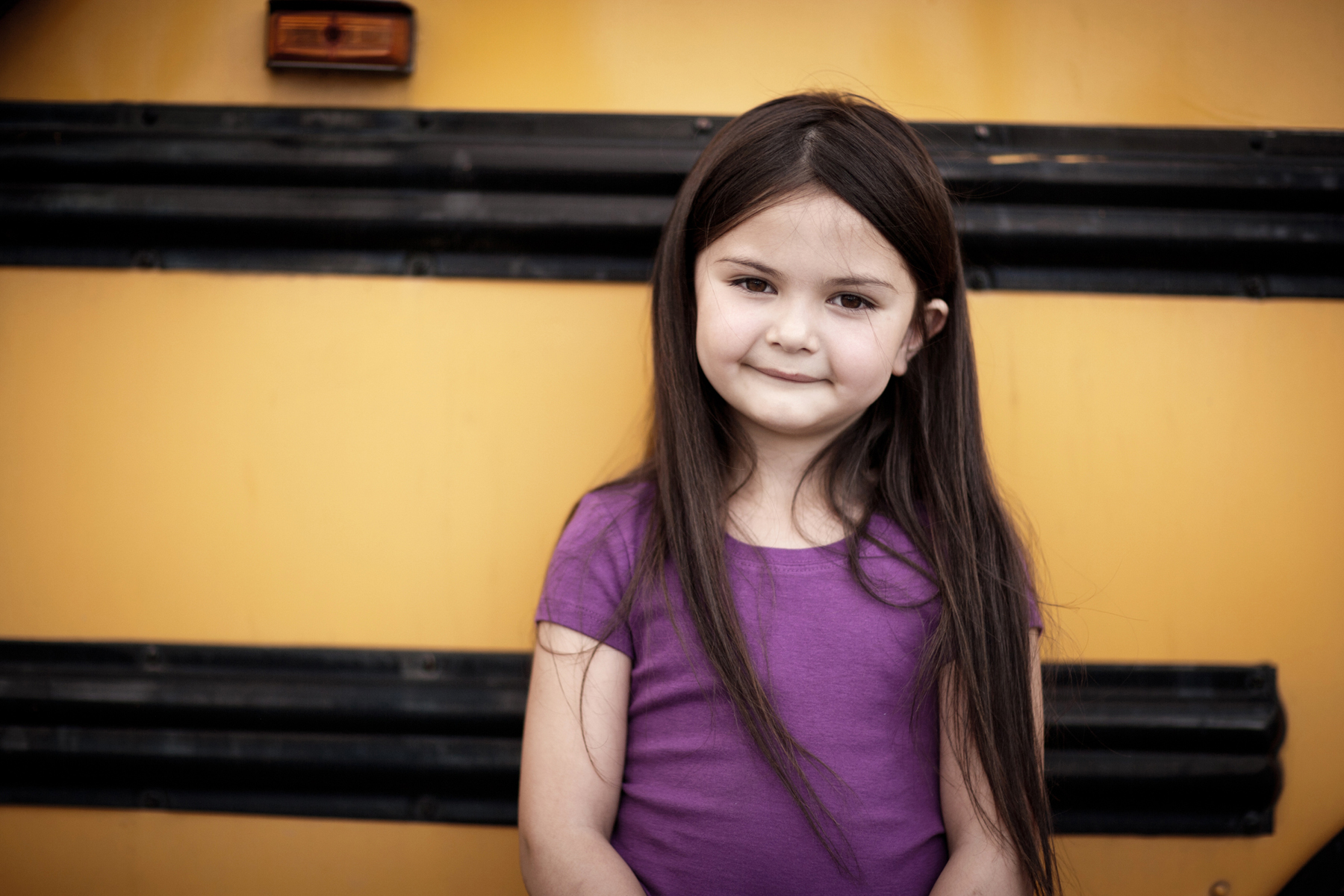 Young girl standing in front of a yellow school bus