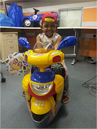 Make-A-Wish International recipient 5 year old Om sitting on his new bike