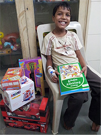 Make-A-Wish International recipient 11 year old Prem holding his new toys, musical instruments and games