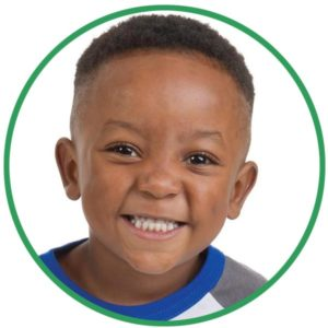 Young boy smiles at the camera inside a green circle