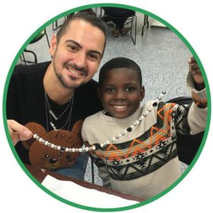 Young boy and volunteer create a beaded necklace