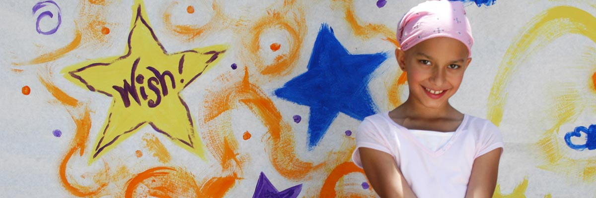 Girl wearing a pink bandanna stands in front of a wall with a star that says