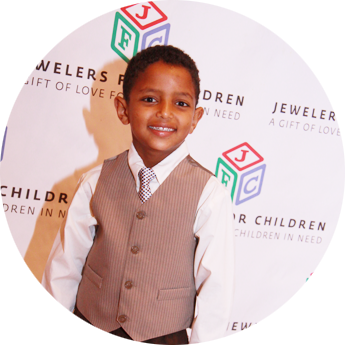 Young boy stands on a red carpet in front of the Jewelers for Children logo