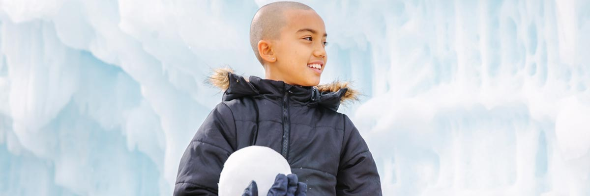Make-A-Wish child recipient Shore standing in front of an ice wall